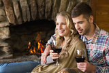 Couple with wineglasses in front of lit fireplace