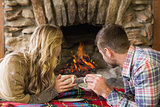 Relaxed couple with tea cups looking at lit fireplace