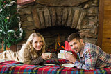 Couple with tea cups in front of lit fireplace