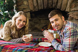 Smiling couple with tea cups in front of lit fireplace