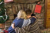 Romantic couple embracing in front of fireplace