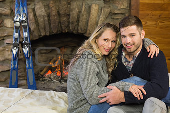 Portrait of a romantic couple in front of lit fireplace