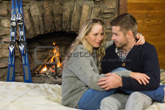 Romantic couple with arms around in front of lit fireplace