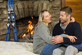 Cheerful couple with arms around in front of lit fireplace