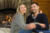 Romantic couple in front of lit fireplace