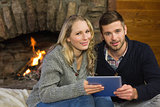 Couple using tablet PC in front of lit fireplace