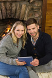 Lovely couple using tablet PC in front of lit fireplace