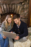 Couple using laptop in front of lit fireplace