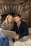 Lovely couple using laptop in front of lit fireplace
