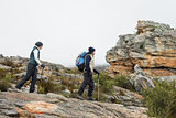 Couple walking through rocky landscape with trekking poles against sky