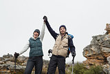 Couple on rocky landscape with hands raised against sky