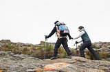 Couple walking on rocky landscape with trekking poles