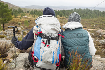 Couple with backpack and trekking pole on a hike
