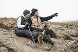 Couple sitting on rock with trekking poles while on a hike