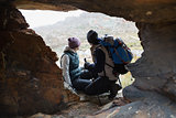 Couple seen through rock cave while on a hike