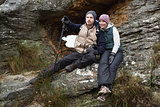 Smiling couple on rock while on a hike