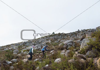 Couple walking through rocky landscape against clear sky