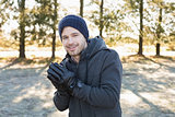 Smiling man in warm clothing shivering while having a walk in forest