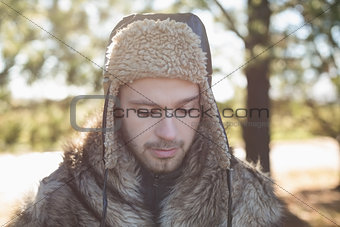 Close up of a man in warm clothing looking down in forest