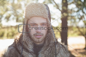 Close up of a handsome man in warm clothing in forest