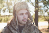 Close up of man in warm clothing looking away in forest
