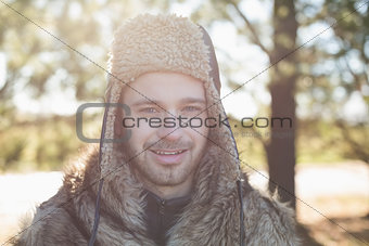 Close up portrait of a smiling man in warm clothing in forest