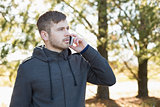 Serious man using mobile phone outdoors
