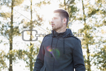 Man in pullover standing in forest against trees