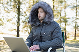 Young man in fur hood jacket using laptop in forest