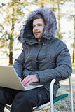 Young man in fur hood jacket using laptop in the forest