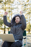 Cheerful man in fur hood jacket with laptop clenching fists in forest