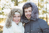 Smiling couple in fur hood jackets in the woods