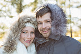 Smiling young couple in fur hood jackets in the woods