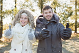 Couple in jackets gesturing thumbs up in the woods