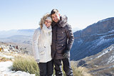 Smiling couple in fur hood jackets against mountain range