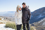 Couple in fur hood jackets against mountain range