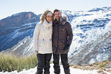Smiling couple in fur hood jackets against snowed mountain range