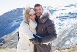 Loving couple in fur hood jackets against snowed mountain range