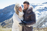 Loving couple in jackets against snowed mountain range