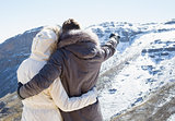 Couple in fur hood jackets looking at snowed mountain range