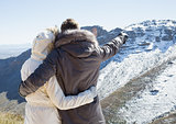 Loving couple in fur hood jackets looking at snowed mountain range