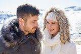 Couple in fur hood jackets against snowed mountain