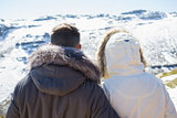 Couple in jackets looking at snowed mountain range