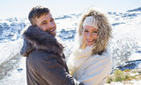 Loving couple in jackets in front of snowed mountain