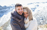 Couple in jackets embracing against snowed mountain