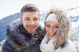 Loving couple in jackets against snowed mountain