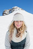 Smiling woman in front of snowed hill and clear blue sky