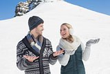 Couple with hands open looking at each other in front of snowed hill