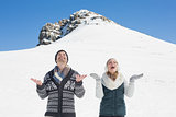 Cheerful couple with hands open looking up in front of snowed hill
