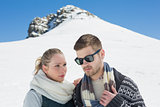 Couple in warm clothing in front of snowed hill